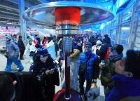 開会式会場のスタンド裏で、ヒーターにあたって暖をとる人たち=韓国・平昌五輪スタジアムで2018年2月9日午後6時22分、手塚耕一郎撮影