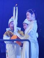 開会式で聖火をアイスホッケー女子南北合同チーム「コリア」の選手から受け取る最終走者の金姸児(キム・ヨナ)さん(手前)=韓国・平昌五輪スタジアムで2018年2月9日、手塚耕一郎撮影