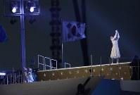 聖火台の前で華麗な滑りを見せた元フィギュアスケート選手の金妍児(キム・ヨナ)さん=平昌五輪スタジアム五輪で2018年2月9日午後10時7分、佐々木順一撮影