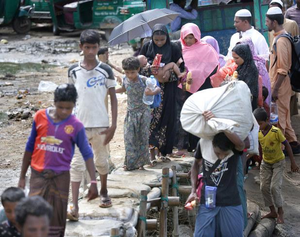 小さな橋を渡って避難するロヒンギャ難民たち=コックスバザール近郊で2017年10月4日、宮武祐希撮影