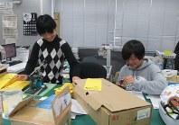 封筒に点字を打ち込む作業を行う早稲田大文化構想学部3年の麓安都美さん(左)と土生りささん