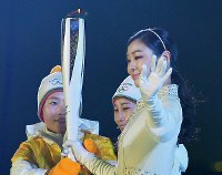 2010 Vancouver Olympic figure skating gold medalist Kim Yuna, right, takes the Olympic torch from two members of the combined Korean Olympic women's hockey team at the opening ceremony of the Pyeongchang Winter Games in Pyeongchang, South Korea, on Feb. 9, 2018. (Mainichi)