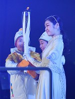 2010 Vancouver Olympic figure skating gold medalist Kim Yuna, right, takes the Olympic torch from two members of the combined Korean Olympic women's hockey team at the opening ceremony of the Pyeongchang Winter Games in Pyeongchang, South Korea, on Feb. 9, 2018. (Mainichi