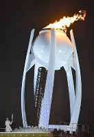 2010 Vancouver Olympic figure skating gold medalist Kim Yuna, bottom left, is seen during the lighting of the Olympic cauldron during the opening ceremony of the Pyeongchang Winter Games in Pyeongchang, South Korea, on Feb. 9, 2018. (Mainichi)