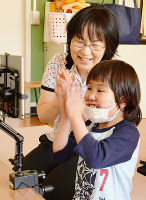 加藤愛美さん(手前)がタブレット端末を操作する様子を見守る赤坂緑教諭=鳥取県米子市上福原7の県立皆生養護学校で、小野まなみ撮影