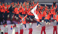 Nordic ski jumper Noriaki Kasai, holding the Japanese flag, leads Team Japan into Pyeongchang Olympic Stadium in Pyeongchang, South Korea, during the opening ceremony of the 2018 Winter Olympics, on Feb. 9, 2018. (Mainichi)