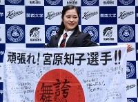 学校関係者の激励メッセージが書かれた日の丸を手に笑顔を見せる宮原知子=吹田市の関大で2018年1月18日午前8時39分、浅妻博之撮影