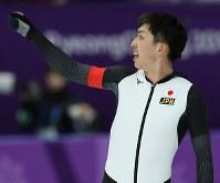 スピードスケート男子5000メートルに出場し、客席からの声援に手を上げて応える一戸誠太郎=江陵オーバルで2018年2月11日、佐々木順一撮影