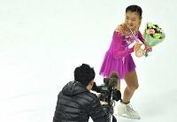 【フィギュアGPファイナル・ジュニア女子フリー】 ジュニア女子シングルで3位に入りテレビカメラに笑顔を見せる坂本花織(右)=フランス・マルセイユで2016年12月9日、宮間俊樹撮影