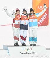 モーグル女子のフラワーセレモニーで記念撮影に応じる優勝したペリーヌ・ラフォン(中央)、2位のジュスティーヌ・デュフールラポワント(左)、3位のユリア・ガリシェワ(右)=フェニックス・スノーパークで2018年2月11日、宮間俊樹撮影