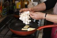 フライパンにバターと刻んだマシュマロを入れ、形がなくなるまでかき混ぜる=根岸基弘撮影