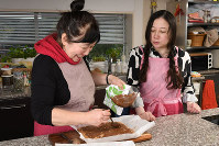 キッチンペーパーを敷いたバットの上で平にし、冷やして固め、湯煎にかけた刻んだチョコレートを上にかけ冷やす=根岸基弘撮影