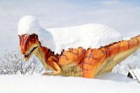 大量の雪が積もった恐竜のモニュメント=福井県勝山市で2018年2月8日、幾島健太郎撮影