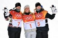 スノーボード女子スロープスタイルで優勝しフラワーセレモニーで笑顔のジェイミー・アンダーソン(中央)。左は2位のローリー・ブルーアン、右は3位のエンニ・ルカヤルビ=フェニックス・スノーパークで2018年2月12日、宮間俊樹撮影
