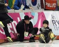 スピードスケートW杯・女子500メートルで転倒してフェンスに激突し、係員から声をかけられる小平奈緒(右)=カルガリーの五輪オーバルで2013年1月19日、藤野智成撮影
