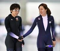 冬季アジア大会・女子500メートルで同走し、笑顔で握手する優勝した小平奈緒(左)と、2位の李相花=北海道帯広市の明治北海道十勝オーバルで2017年2月21日、手塚耕一郎撮影