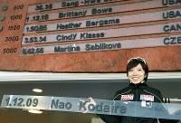 女子1000メートル世界新記録のボードを手に、会場のユタ五輪オーバルにある世界記録一覧の前で笑顔を見せる小平奈緒=米国・ソルトレークシティーで2017年12月10日、佐々木順一撮影