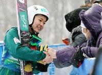 【スキージャンプW杯女子】5位となり観客と握手する高梨沙羅(左)=札幌市宮の森ジャンプ競技場で2013年2月3日、貝塚太一撮影