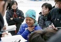 スキージャンプW杯の練習後、のどを押さえて記者の質問に答える高梨沙羅(中央)=札幌市宮の森ジャンプ競技場で2014年1月8日、貝塚太一撮影