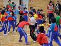児童らと「しっぽ取り競争」をして遊ぶ高梨沙羅さん(中央)=山田町立船越小で2014年4月28日、鬼山親芳撮影