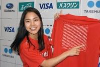 羽田空港に帰国し、全日本スキー連盟が販売するTシャツにプリントされた自分の名前を指さす高梨沙羅=羽田空港で2017年12月19日、江連能弘撮影