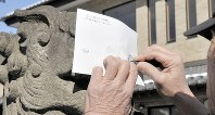 狛犬の鼻に紙を押しつけ、鉛筆で狛拓を取る吉野忠夫さん=さいたま市大宮区で