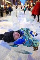 すすきの会場の乗り物の氷像で遊ぶ男の子=札幌市中央区で2018年2月7日、梅村直承撮影