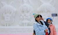 「けものフレンズ」の雪像前でセルフィを撮るアジアから訪れた家族=札幌市中央区で2018年2月5日、梅村直承撮影