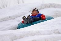つどーむ会場の雪の滑り台で遊ぶ子ども=札幌市東区で2018年2月8日、梅村直承撮影