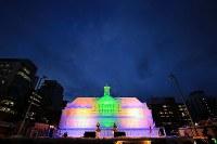 ステージで熱の入ったパフォーマンスが繰り広げられる中、鮮やかに輝く大氷像「台湾・旧台中駅」=札幌市中央区で2018年2月8日、梅村直承撮影