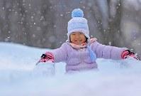 雪と氷の滑り台を笑顔で滑る女の子=札幌市中央区で2018年2月5日、梅村直承撮影