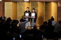 国民栄誉賞を授与され、盾を手に笑顔を見せる羽生善治氏(左)と井山裕太氏=東京都千代田区で2018年2月13日、小川昌宏撮影