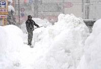 激しく雪が降る中、除雪作業する人=福井市で2018年2月13日午前11時38分、平川義之撮影