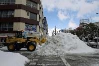 交差点付近に除雪で集められた雪=福井市で2018年2月13日午後2時13分、平川義之撮影