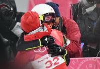 スキージャンプ女子、2回目の飛躍を終えて、伊藤有希(手前)と抱き合う高梨沙羅=アルペンシア・ジャンプセンターで2018年2月12日、山崎一輝撮影