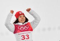 スキージャンプ女子ノーマルヒル3位となりフラワーセレモニーで笑顔で表彰台にあがる高梨沙羅=アルペンシア・ジャンプセンターで2018年2月12日、宮間俊樹撮影