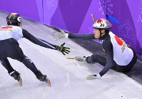 【平昌五輪】ショートトラック男子5000メートルリレー予選で、坂爪亮介(右)が転倒。タッチしにいく渡辺啓太=江陵アイスアリーナで2018年2月13日、手塚耕一郎撮影