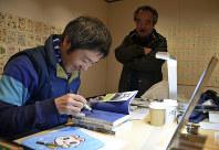 来場者にサインを求められ、「仕事机」で著書にペンを走らせるながさわたかひろさん=東根市のまなびあテラスで2018年2月9日、野間口陽撮影