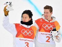 Japan's Ayumu Hirano, left, and Shaun White of the United States respond to cheers from spectators during the flower ceremony at Phoenix Snow Park in Pyeongchang, South Korea, on Feb. 14, 2018, after White won gold and Hirano came in second in the men's snowboard halfpipe. (Mainichi)
