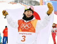 Ayumu Hirano holds up the Japanese flag after winning an Olympic silver medal in the men's snowboard halfpipe at Phoenix Snow Park in Pyeongchang, South Korea, on Feb. 14, 2018. (Mainichi)