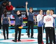 米国との初戦に勝利し、客席からの声援に手を振って応える藤沢五月(左)と吉田知那美=江陵カーリングセンターで2018年2月14日、佐々木順一撮影