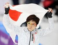 スピードスケート女子1000メートルで銀メダルを獲得し、日の丸を掲げる小平奈緒=江陵オーバルで2018年2月14日、佐々木順一撮影