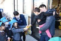 買い物客にチラシ入りチョコを手渡す園児ら