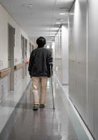 つえをついて病院内を歩く三輪晴美記者=篠田英美さん撮影