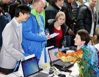 ソチ国際空港到着後、選手証の登録のため担当者と笑顔で話をする羽生結弦(左)=ロシア・ソチで2014年2月3日午後9時10分、貝塚太一撮影