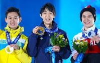 ソチ五輪で、金メダルを手にして笑顔の羽生(中央)。右は2位のチャン(カナダ)、左は3位のテン(カザフスタン)=ロシア・ソチの五輪公園で2014年2月15日、山本晋撮影