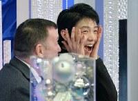 NHK杯の男子フリーの演技後、自らの得点結果に驚いた表情の羽生結弦選手。左はブライアン・オーサー・コーチ=長野市のビッグハットで2015年11月28日、宮間俊樹撮影