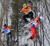 【平昌五輪】スノーボード男子クロス決勝トーナメント1回戦で滑る優勝したピエール・ボルティエ(右)。中央は2位に入ったジャリッド・ヒューズ=フェニックス・スノーパークで2018年2月15日、宮間俊樹撮影
