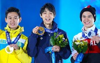 Yuzuru Hanyu, center, smiles holding the gold medal he won at the Sochi Winter Olympics on Feb. 15, 2014. Flanking Hanyu are silver medalist Patrick Chan of Canada, right, and bronze medalist Dennis Ten of Kazakhstan. (Mainichi)
