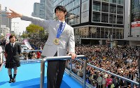 Figure skater Yuzuru Hanyu waves to fans from a parade float in Sendai's Aoba Ward on April 26, 2014. (Pool photo)